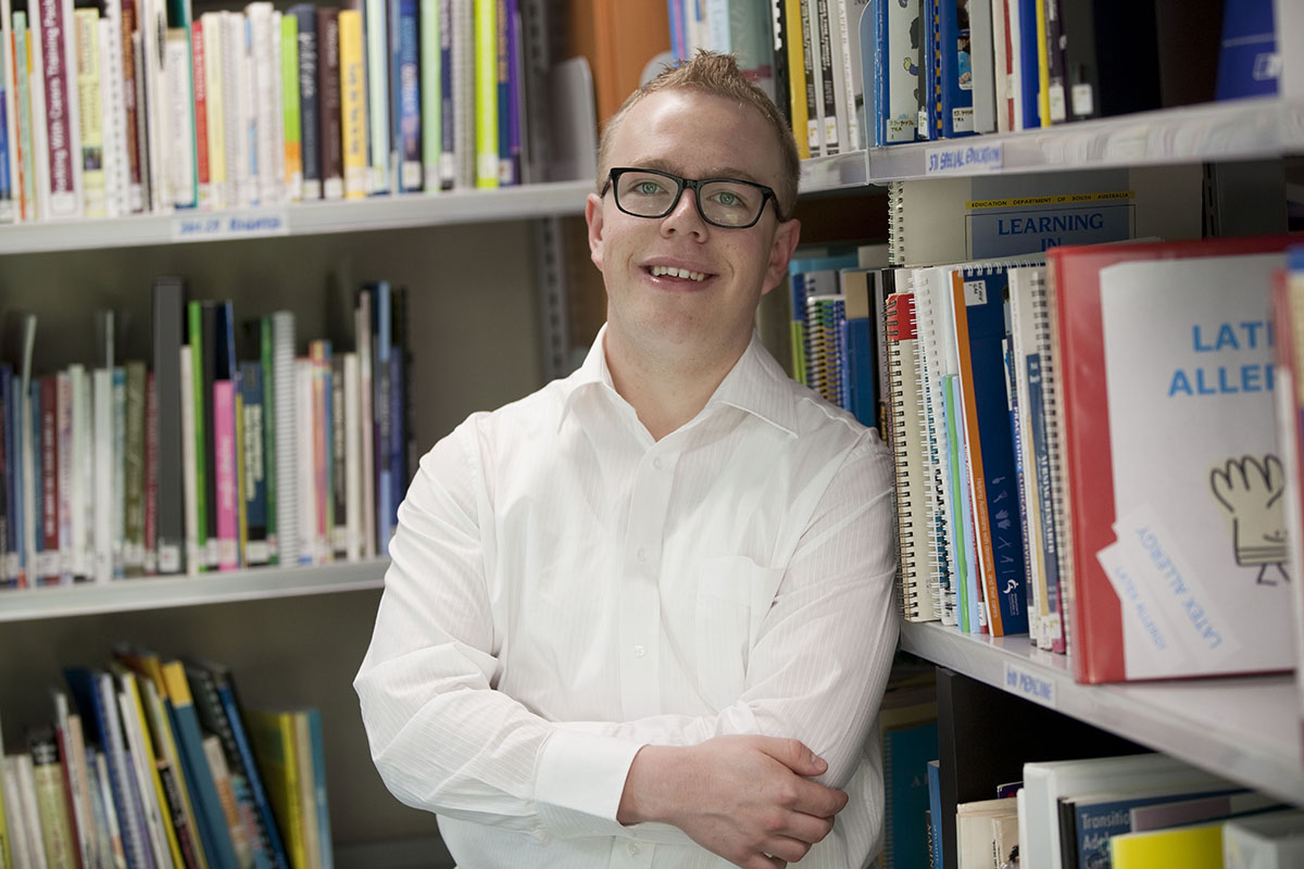 A young man standing in the corner of the library with his arms crossed and smiling at the camera.