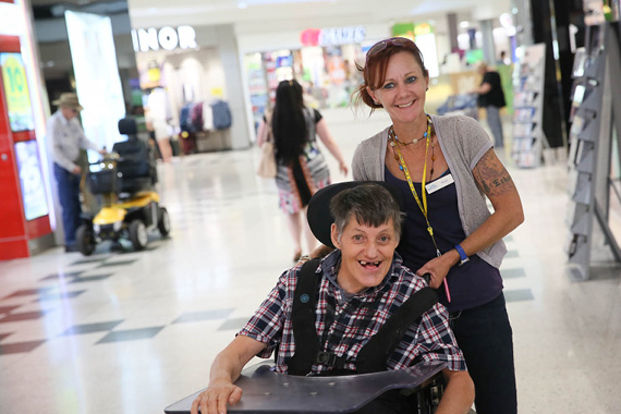 A man with disability receiving support in the community, from a female support worker